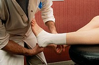 BANDAGE<BR>Photo essay. Model and health professional. <BR>Physical therapist. Strapping. Soft splinting of the tibio-tarsal joint.