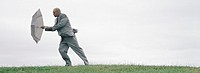 Man walking into wind with open umbrella shielding him, full length