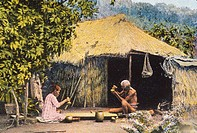 c.1900 Senior local couple pounding poi sitting in front of straw hut, lush greenery, postcard