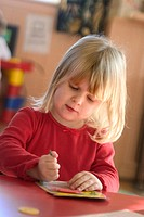 Three year old girl blond hair sitting at table drawing