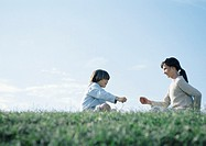 Boy and girl sitting on grass playing rock paper scissors