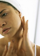 Young woman touching bare neck, looking away