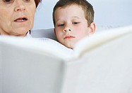 Grandmother reading book to boy