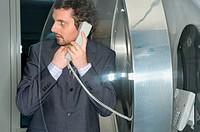 Businessman using pay telephone