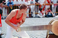 ´Trontzalariak´ slicing a log with a ´tronza´ saw, rural basque sport event. Pamplona. Navarra, Spain