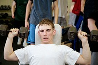 Students work out in a weight trainning room in a high school class