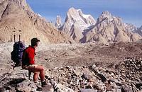 Trekker on Baltoro glacier, unnamed Trango spire behind. Karakoram mountains, Pakistan