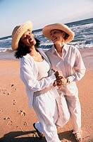 Two women walking on the beach holding hands