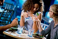 Two young women eating in a cafe with an unrecognized person
