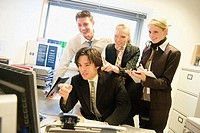Group of young people, in an office all looking at the computer, smiling and pointing