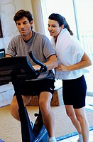 Young woman and a young man exercising in a gym