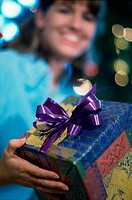 Mid adult woman holding a gift smiling