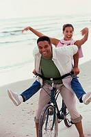 Portrait of a young couple riding a bicycle on the beach