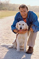 Portrait of a mature man holding his dog