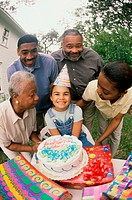 Girl celebrating her birthday with her parents and grandparents