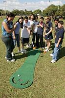 Hispanic students, golf putting game. North Shore Park, North Beach, Miami Beach, Florida. USA.