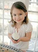 Small girl with a chocolate cup-cake