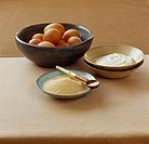 Granulated sugar, eggs and crème fraîche in bowls