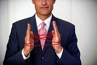mature businessman doing the cat´s cradle with a red woolen thread