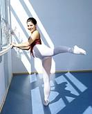 Young dancer doing an arabesque at ballet barre