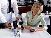 woman working with electronic organizer while being served in restaurant