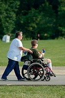 Handicapped adults ride in a battery powered wheelchair while attending a festival