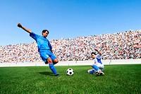 Soccer player kicking ball as defender slides in