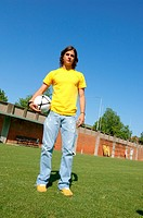 Young man in casual wear holding soccer ball
