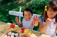 Girls painting eggs and hands