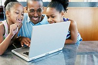 Father and daughters with laptop