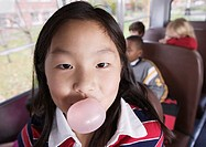 Close up portrait of girl blowing bubble