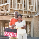 Portrait of couple standing by sold sign