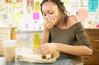 Woman eating sandwich in cafe