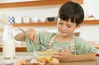 Boy mixing eggs