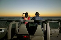 A couple watches the sunset from their car