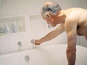An elderly man drawing a bath