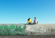 Teen couple sit on a graffiti-covered wall