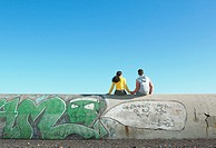 Teen couple sitting on a graffiti-covered wall