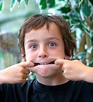 Portrait of a boy stretching the sides of his mouth