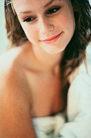 Young woman wrapped in a towel smiling