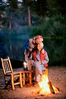 Senior couple hugging each other beside a camp fire