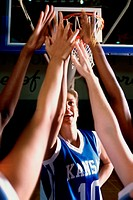 Female basketball players reaching upwards