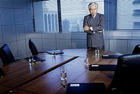 Businessman leaning on a conference table