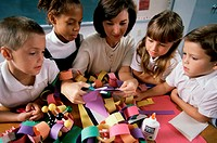High angle view of a female teacher teaching her students arts and crafts