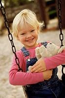 Portrait of a girl sitting on a swing holding a teddy bear