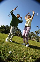 Low angle view of a mid adult man and a mid adult woman at a golf course