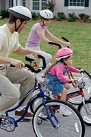 Young couple cycling with their daughter
