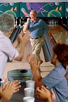 Senior man at a bowling alley with a senior couple applauding him