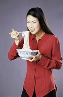 Portrait of a young woman eating a bowl of noodles
