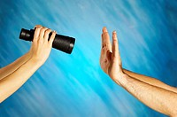 Woman´s hands holding a pair of binoculars with a man´s hands in front of it